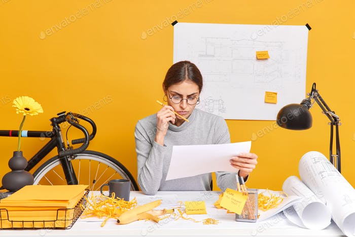 Serious successful skilled woman designer creats new architect sketches concentrated attentively in