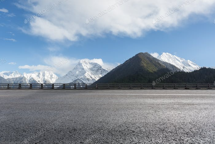 empty asphalt highway with snow mountain background