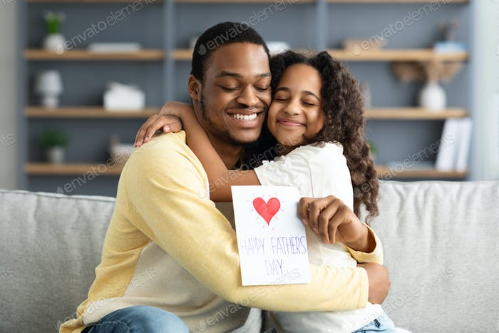 Cute black girl hugging her father, celebrating Fathers Day
