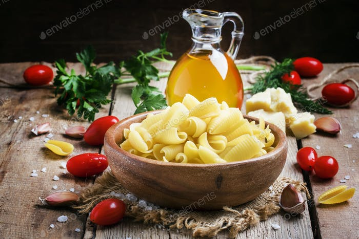Ingredients for cooking pasta, old wooden table