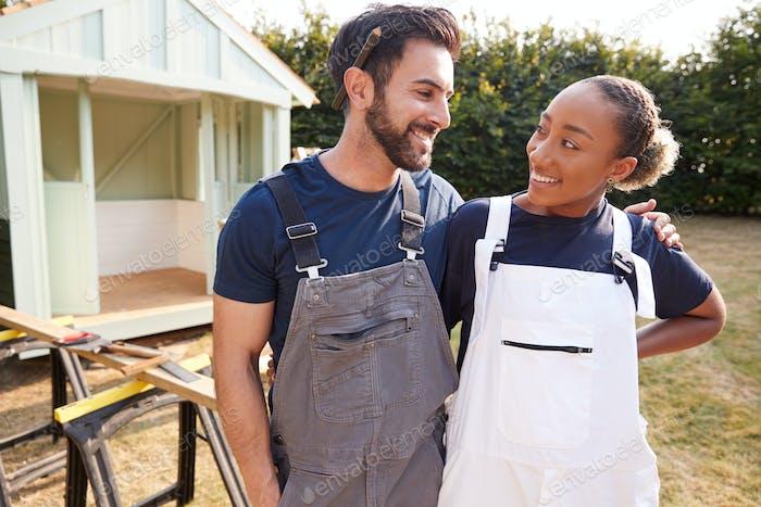 Couple Taking A Break From Building Outdoor Summerhouse In Garden