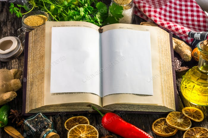 Open recipe book with  ingredients on wooden background