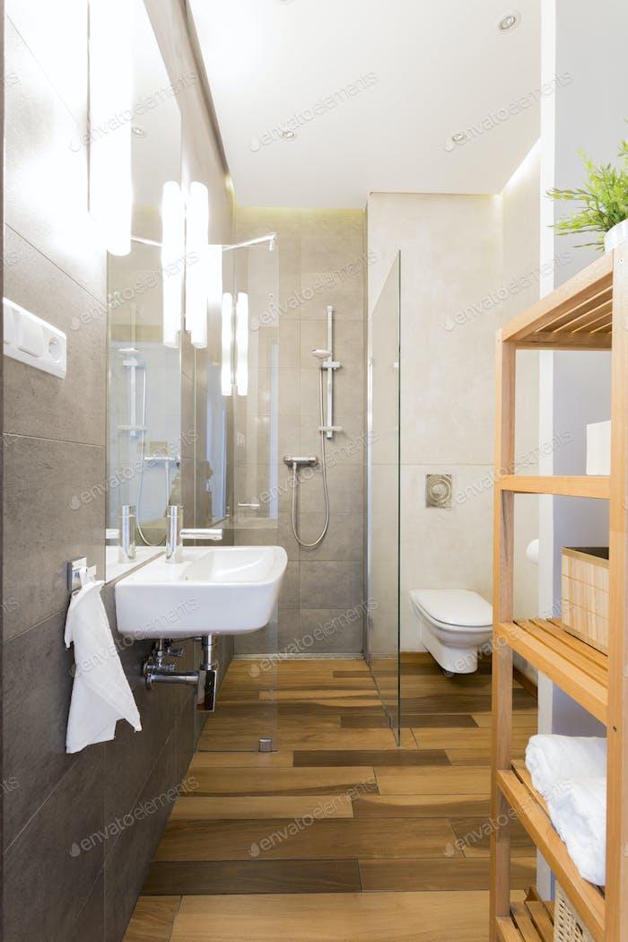 Narrow loft bathroom with wooden floor