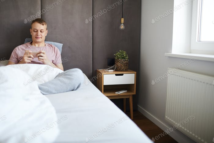 Happy relaxed guy watching curious video in smartphone in bed