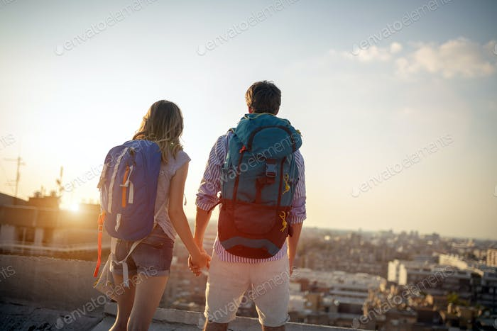 Multiethnic traveler couple using map together on sunny day