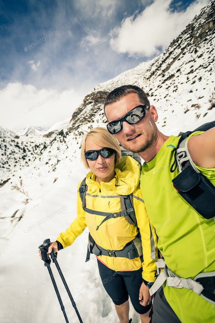 Couple hikers, partnership and teamwork in winter mountains