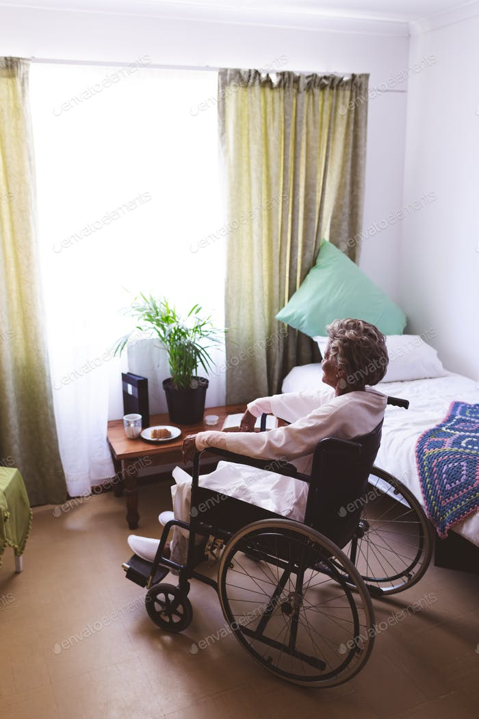 Thoughtful senior woman sitting on wheelchair looking at window at nursing home