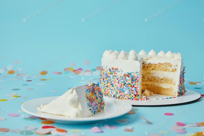 Scheibe Kuchen mit geschnittenem Kuchen auf blauem Hintergrund mit Konfetti