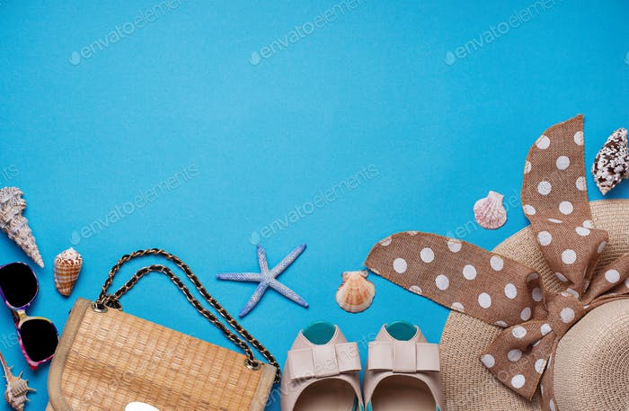 Straw hat, sunglasses and shoes on blue background