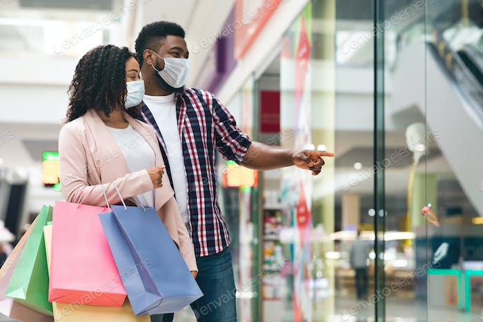 Shopping during coronavirus outbreak. Black couple wearing medical face masks in mall