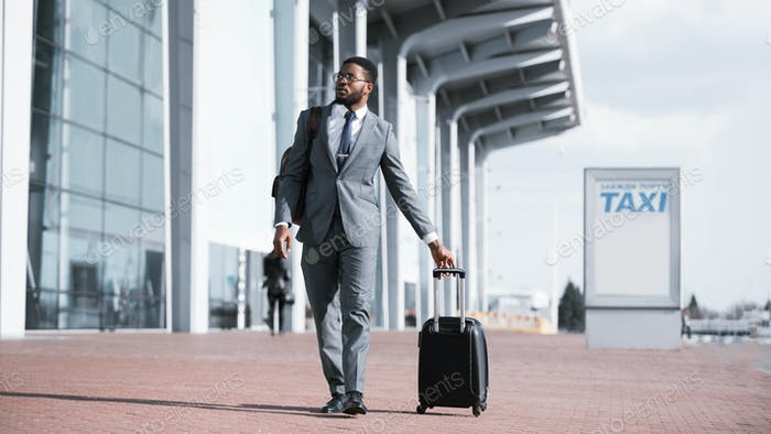 Black Businessman Walking With Suitcase Near Airport Taxi Parking, Panorama