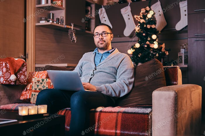 Happy man in glasses hold laptop and looking at camera while sitting on sofa at Christmas time.