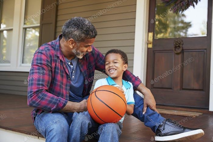 Vater und Sohn diskutieren Basketball auf Veranda von zu Hause