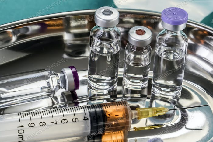 Some Vials And Syringe On Operating Table