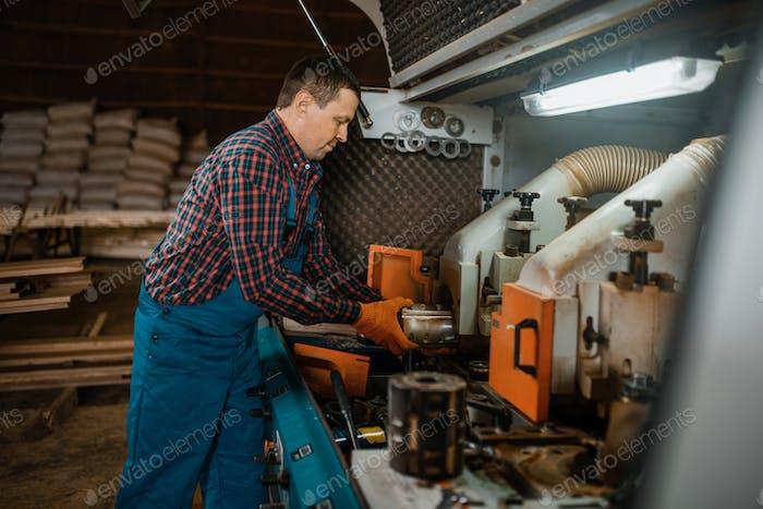 Zimmermann in Uniform in der Nähe von Holzbearbeitungsmaschine
