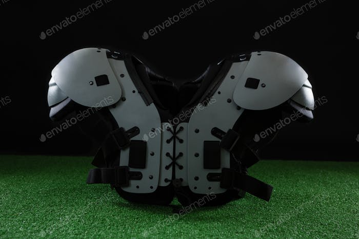 American football shoulder pads over artificial turf