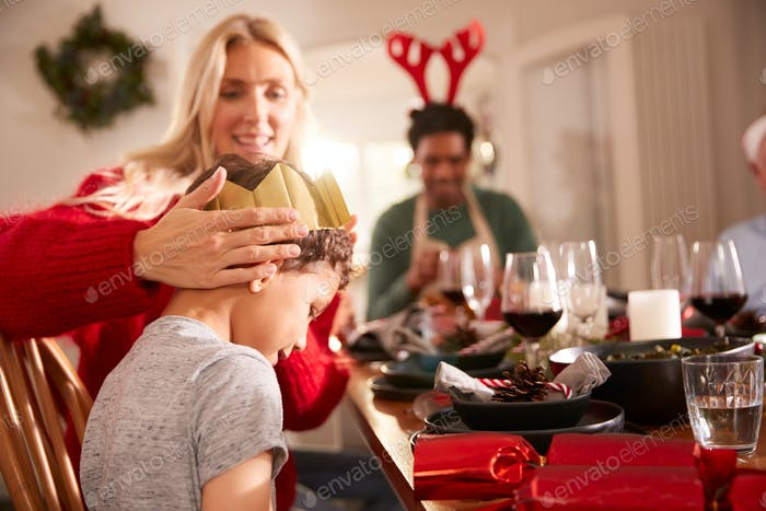 Madre poniendo corona de papel en el hijo como la familia se sienta para la comida de Navidad y galletas abiertas