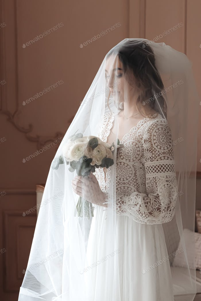 Portrait of a young bride covered with a wedding veil holding a bouquet.
