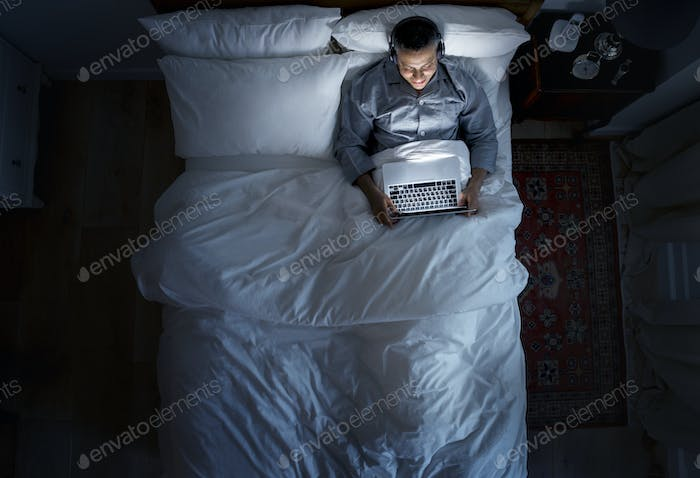 Man on bed using his laptop and a headphone