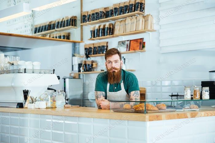 Barista mit Bart und Schnurrbart stehend im Café