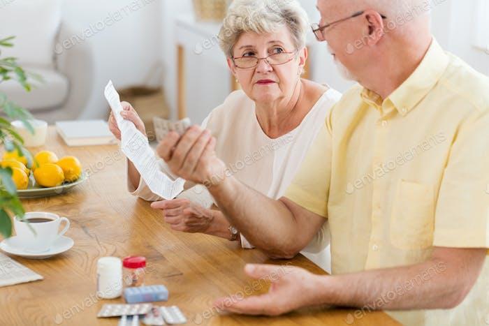 Senior woman reading leaflet of a drug and elderly man holding p