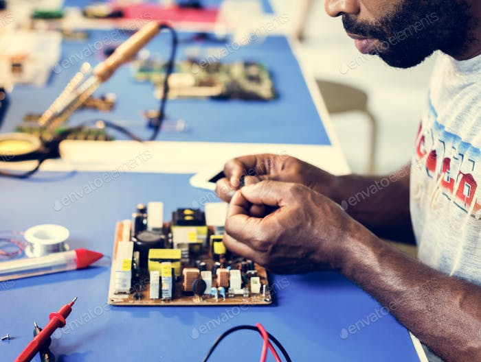 Electrical technician working on electronic board