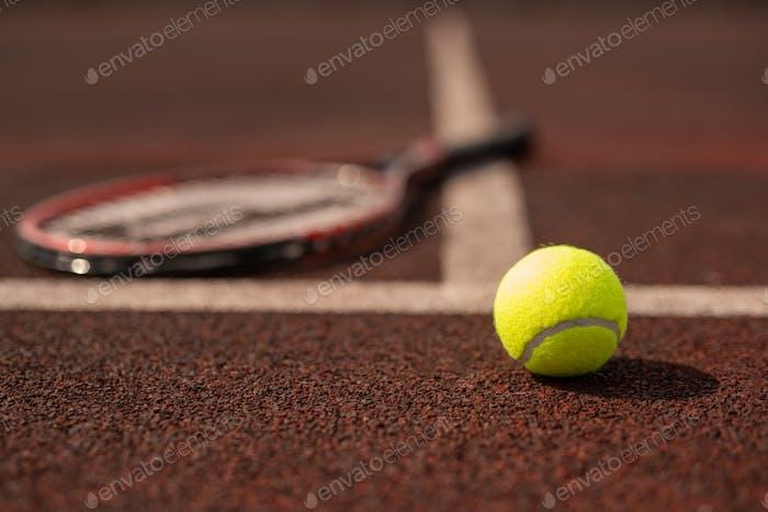 Tennis ball on sports playground on stadium by white line