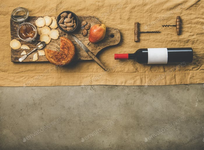 Wine bottle, vintage corkscrews and appetizers board, copy space