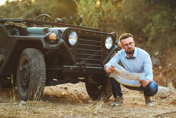 Junge stilvolle Mann mit Brille und Fliege sehen Sie die Karte in der Nähe der