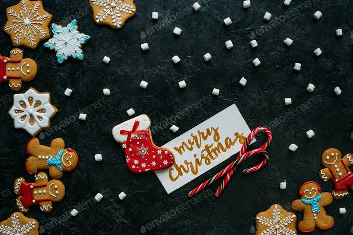 top view of homemade gingerbreads, marshmallows, candy canes and merry christmas greeting card on