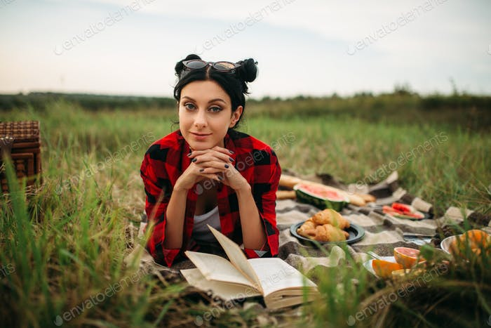 Woman with book lies on plaid, picnic in field