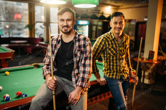 Two male billiard players with cues poses