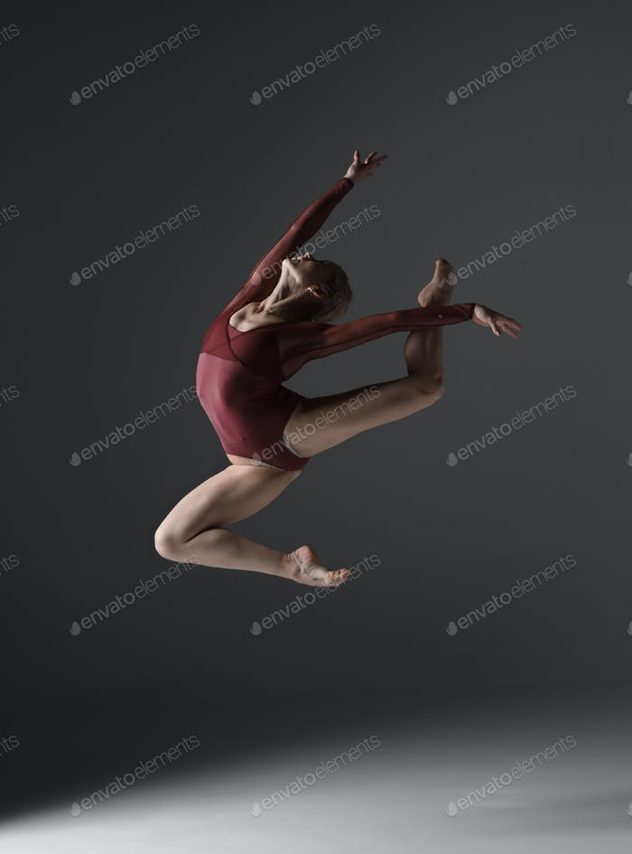 Young beautiful modern style dancer jumping on a studio background