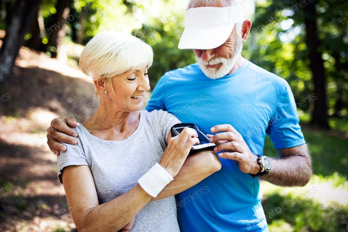 Senior couple jogging and running outdoors in nature