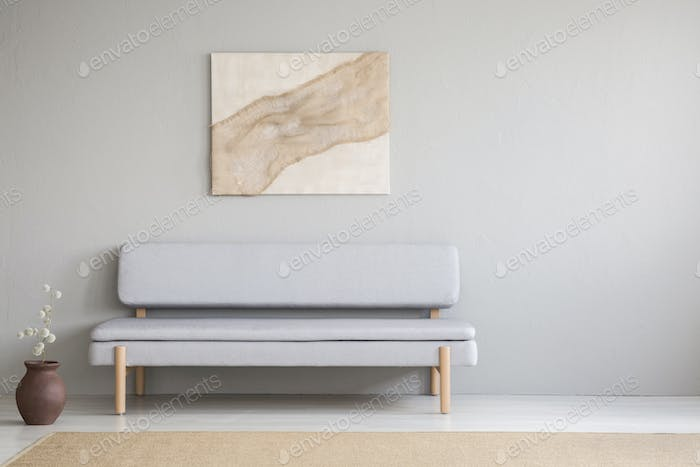 Painting above grey settee in minimal living room interior with