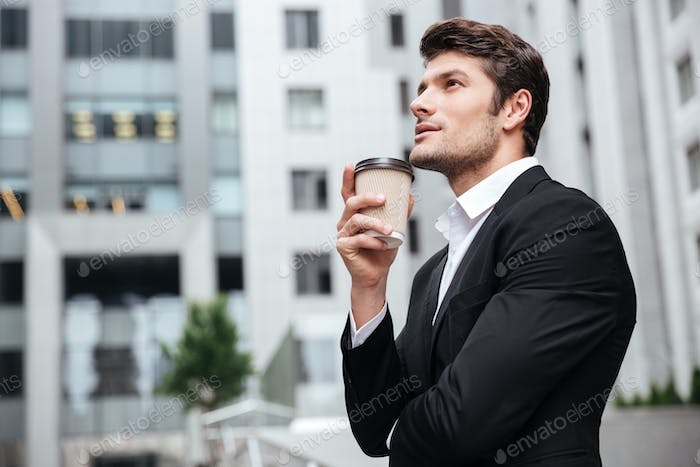 Thoughtful young businessman drinking take away coffee and thinking