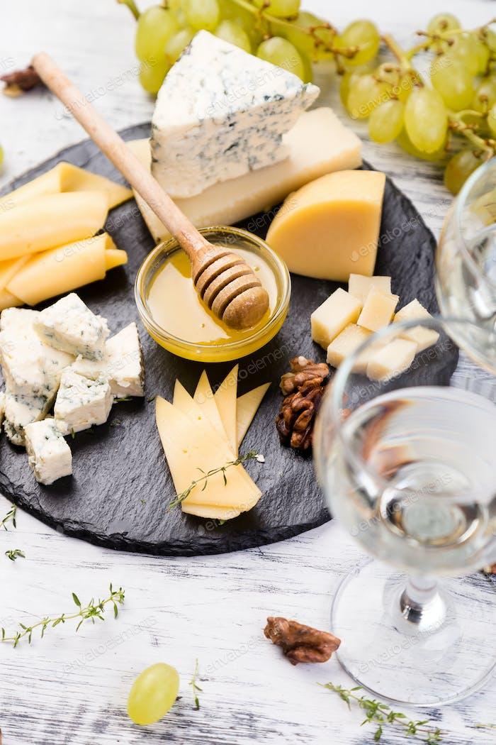 Käseplatte Sortiment von Käse mit Walnüssen, Brot und Honig auf Steinschieferplatte.