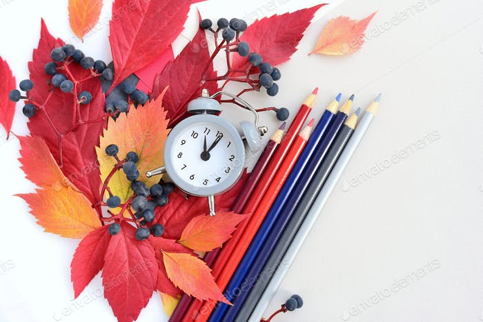 Autumn background with an alarm clock, pencils, sheets of paper