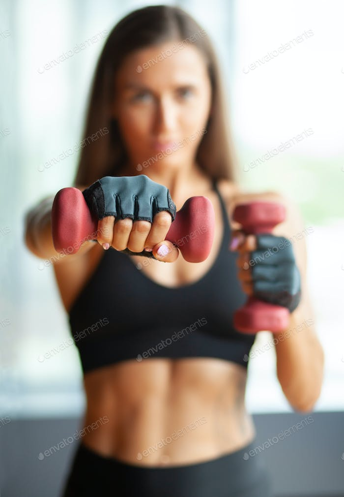 hands with dummbells, defocused sportswoman