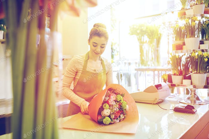 smiling florist woman packing bunch at flower shop