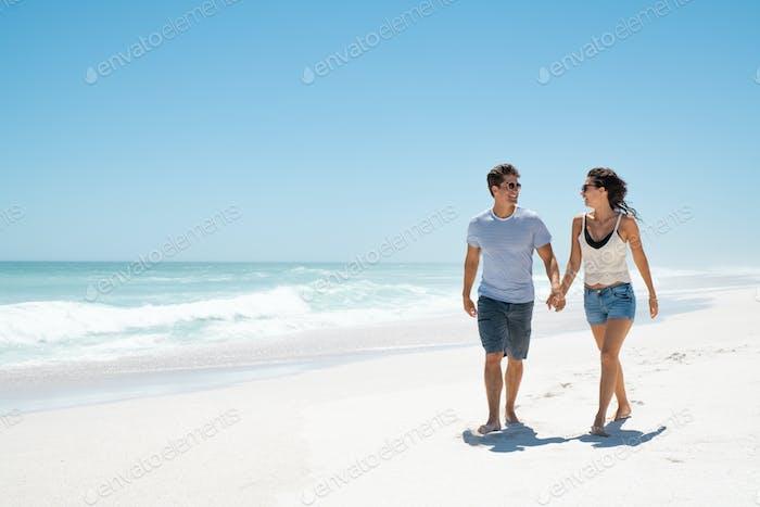 Junges glückliches Paar zu Fuß am Strand