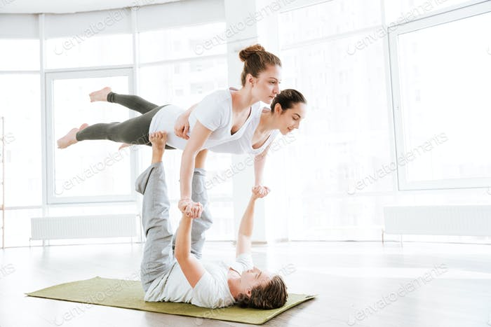 Group of two young women and man doing acro yoga