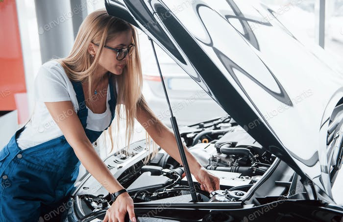 Technical difficulties. On the lovely job. Car addicted woman repairs black automobile indoors
