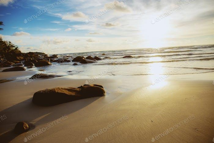 Rocks on sand beach with sunrise