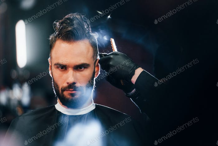 Young bearded man sitting and getting haircut in barber shop