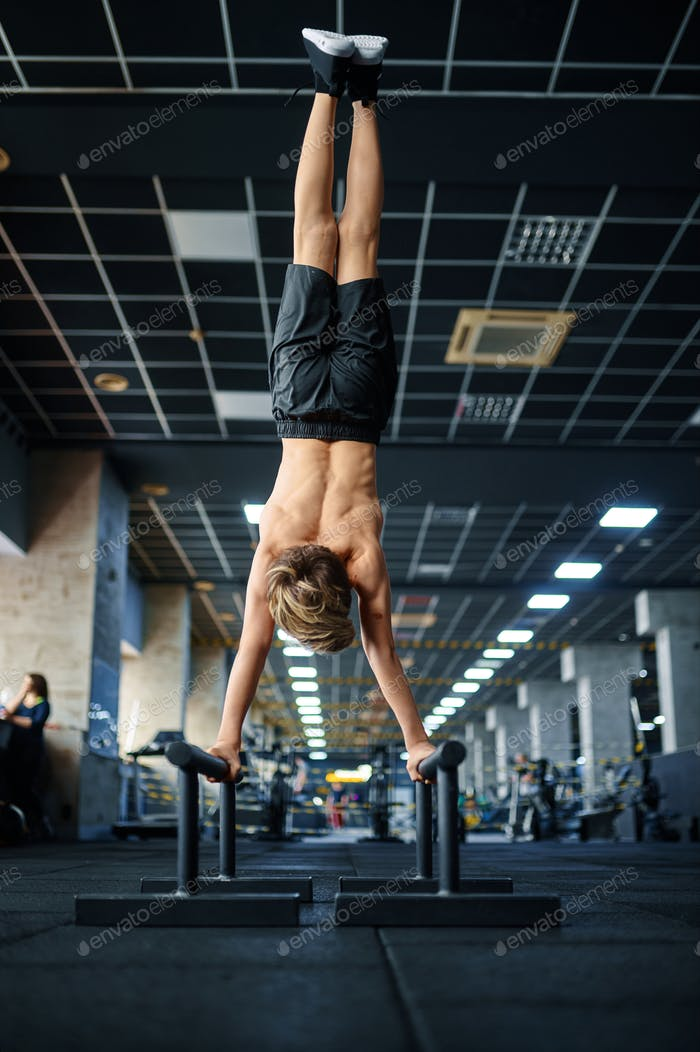 Athletic boy doing exercise on uneven bars in gym