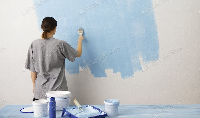Woman painting interior wall with paint roller in new house