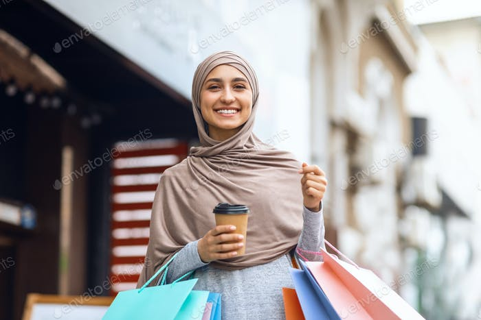 Smiling young woman in hijab holding colorful shopping bags