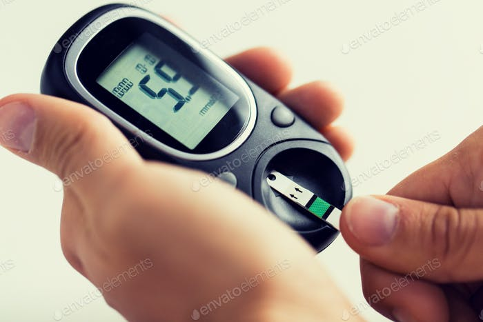 close up of man checking blood sugar by glucometer