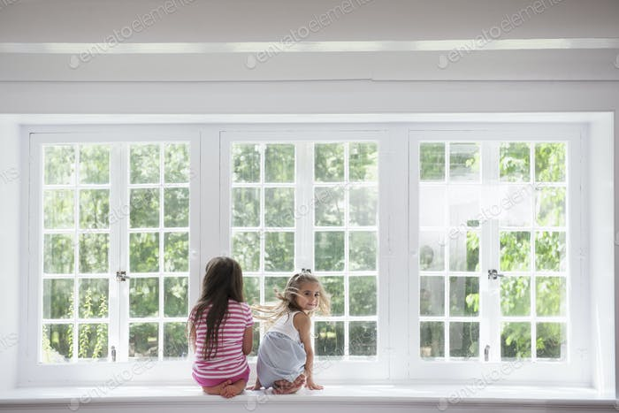 Two girls sitting side by side by a large window.